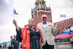 Первомайская демонстрация в Москве на Красной площади. Москва, пенсионеры, пожилая пара, москвичи, флаг россии, красная площадь