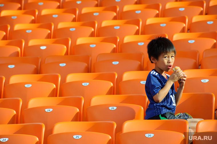 ЧМ-2018. 32 матч Чемпионата мира по футболу между сборными Японии и Сенегала. Екатеринбург, трибуна болельщиков, японец, мальчик, ребенок, еда, фастфуд