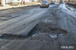 Разбитая дорога по улице Станционная в Кургане.