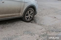 Состояние дорог города Кургана, разбитая дорога, колесо автомобиля, ямы в асфальте