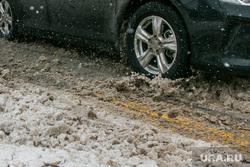 Город в снегу. Курган, колесо автомобиля, мокрый снег, нечищенная дорога