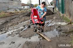 Поселок Восточный. Курган, грязь, женщина с коляской