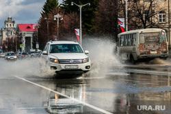 Город после дождя. Курган, лужа на дороге, брызги от автомобиля, улица гоголя