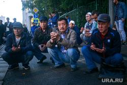 Праздничный намаз в Курбан Байрам у Соборной мечети. Москва, мигранты, мусульмане, гастарбайтеры, сидят на корточках