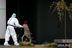 Доставка пациентов скорой помощью в ГКБ №40 «Коммунарка» во время пандемии SARS-CoV-2. Москва, защитный костюм, врачи, скорая помощь, инвалидное кресло, фельдшер, медики, covid19, коронавирус, ковид, противочумной костюм, кресло-каталка, карантинный центр