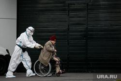 Доставка пациентов скорой помощью в ГКБ №40 «Коммунарка» во время пандемии SARS-CoV-2. Москва, защитный костюм, врачи, скорая помощь, инвалидное кресло, фельдшер, медики, covid-19, коронавирус, ковид, противочумной костюм, кресло-каталка, карантинный центр
